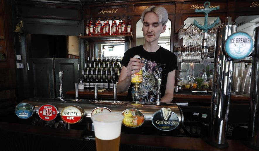 A barman pours a beer at the Crabtree Pub in London, Tuesday, June 23, 2020. Millions of people in Britain will be able to go to the pub, visit a movie theater, get a haircut or attend a religious service starting July 4, in a major loosening of coronavirus lockdown restrictions. The government also announced that from July 4 people will be advised to stay at least 1 meter (3 feet) apart, rather than 2 meters -- as long as they take other measures to reduce transmission of the virus, such as wearing a mask in enclosed spaces. (AP Photo/Frank Augstein)