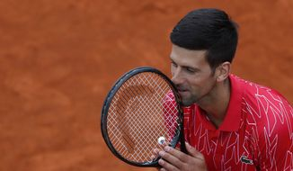 In this Friday, June 12, 2020 photo, Serbia's Novak Djokovic reacts during a tennis doubles match with Jelena Jankovic against Serbia's Nenad Zimonjic and Olga Danilovic at charity tournament Adria Tour, in Belgrade, Serbia. Novak Djokovic has tested positive for the coronavirus after taking part in a tennis exhibition series he organized in Serbia and Croatia. The top-ranked Serb is the fourth player to test positive for the virus after first playing in Belgrade and then again last weekend in Zadar, Croatia. His wife also tested positive. (AP Photo/Darko Vojinovic) ** FILE **