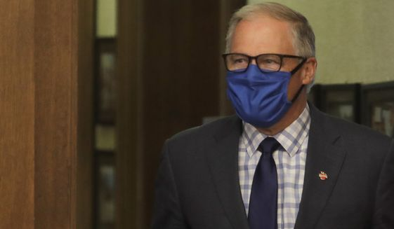 Washington Gov. Jay Inslee wears a face mask as he arrives to speak at a news conference, Tuesday, June 23, 2020, at the Capitol in Olympia, Wash. Inslee announced Tuesday that Washington state will require people to wear facial coverings in most indoor and outdoor public settings, under a statewide public health order in response to ongoing COVID-19 related health concerns. (AP Photo/Ted S. Warren)