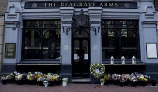 Flowers stand placed outside the Blagrave Arms pub near the scene of a fatal multiple stabbing attack in Forbury Gardens park, in Reading, England, Tuesday, June 23, 2020. The English town of Reading is mourning for three people stabbed to death on Saturday in what is being treated as a terror attack. (AP Photo/Matt Dunham)