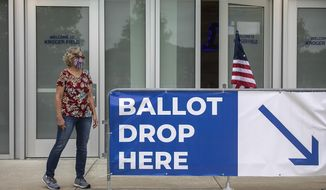Poll worker Dolores Louallen directs Fayette County voters where to drop off their absentee ballots at Kroger Field in Lexington, Ky., on Tuesday, June 23, 2020. (Ryan C. Hermens/Lexington Herald-Leader via AP)