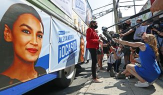 U.S. Rep. Alexandria Ocasio-Cortez, D, New York, center, meets a cluster of media beside a campaign truck plastered with her promotional material in Astoria, Queens, Tuesday, June 23, 2020, on primary election day in New York. (AP Photo/Kathy Willens)