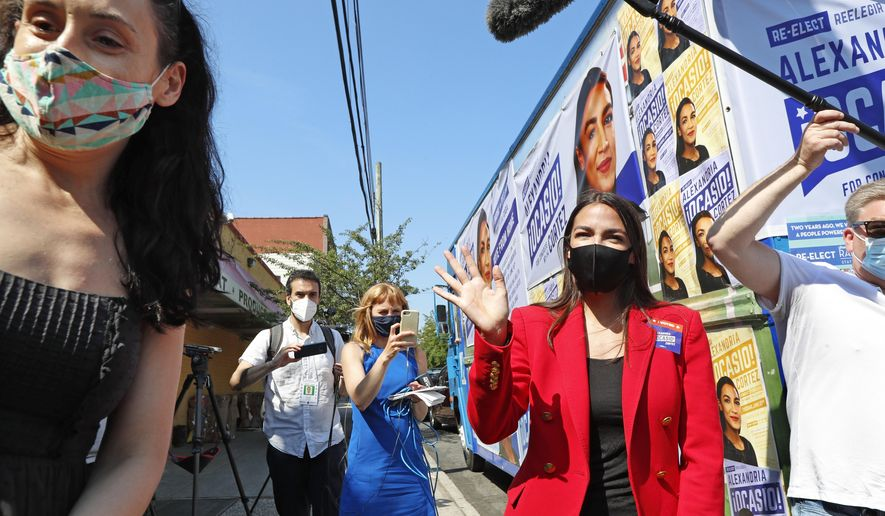 U.S. Rep. Alexandria Ocasio-Cortez, D, New York, center, right, waves as she departs after greeting voters and speaking to a cluster of media during a campaign stop in Astoria, Queens, Tuesday, June 23, 2020, on primary election day in New York. The first-term congresswoman is facing several challengers as she tries to hold on to her position. (AP Photo/Kathy Willens)