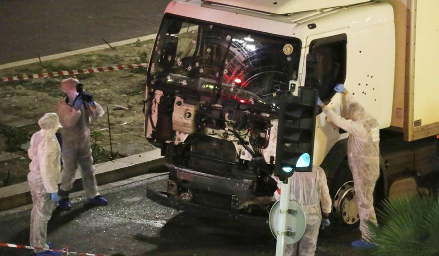 FILE - In this July 14, 2016 file photo, authorities investigate a truck after it plowed through Bastille Day revellers in the French resort city of Nice, southern France. France's counter-terrorism prosecutors have requested nine suspects to be send to trial in connection with the 2016 Bastille Day truck attack in Nice that left 86 people dead. (Sasha Goldsmith via AP, File)