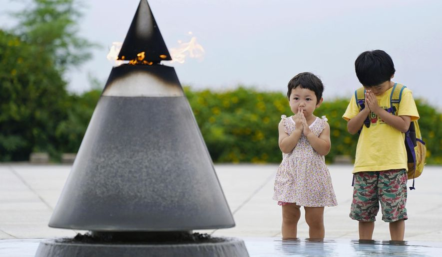 "Children pray in front of the ""Peace of Fire"" at the Peace Memorial Park in Itoman, Okinawa, Japan, Tuesday, June 23, 2020. Okinawan people find it unacceptable that their land is still occupied by a heavy U.S. military presence even 75 years after World War II. They have asked the central government to do more to reduce their burden, and Japanese Prime Minister Shinzo Abe's government repeatedly say it is mindful of their feelings, but the changes are slow to come. (Koji Harada/Kyodo News via AP)"