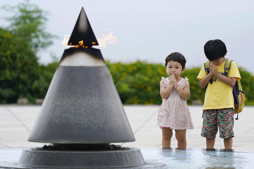 """Children pray in front of the """"Peace of Fire"""" at the Peace Memorial Park in Itoman, Okinawa, Japan, Tuesday, June 23, 2020. Okinawan people find it unacceptable that their land is still occupied by a heavy U.S. military presence even 75 years after World War II. They have asked the central government to do more to reduce their burden, and Japanese Prime Minister Shinzo Abe's government repeatedly say it is mindful of their feelings, but the changes are slow to come. (Koji Harada/Kyodo News via AP)"""