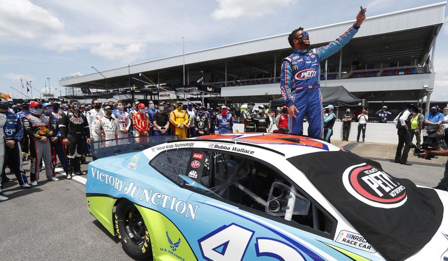 In this June 22, 2020, file photo, Bubba Wallace takes a selfie of himself and of other drivers who had pushed his car to the front in the pits at Talladega Superspeedway before the NASCAR Cup Series auto race in Talladega Ala., Monday, June 22, 2020. The noose found hanging in Wallace's garage stall at Talladega had been there since at least last October, federal authorities said Tuesday, June 23, in announcing there will be no charges filed in an incident that rocked NASCAR and its only fulltime Black driver. (AP Photo/John Bazemore, File)
