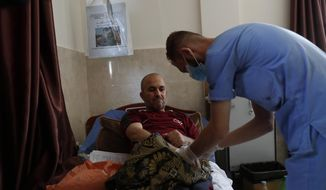 In this Tuesday, June 16, 2020 photo. Palestinian nurse checks a cancer patient Jehad al-Qedra, 52, while he received his treatment at a hospital in Khan Younis refugee camp, Gaza Strip. The Palestinian Authority's decision to cut all ties with Israel was intended to make it pay a price for pressing ahead with plans to annex parts of the occupied West Bank. (AP Photo/Adel Hana)
