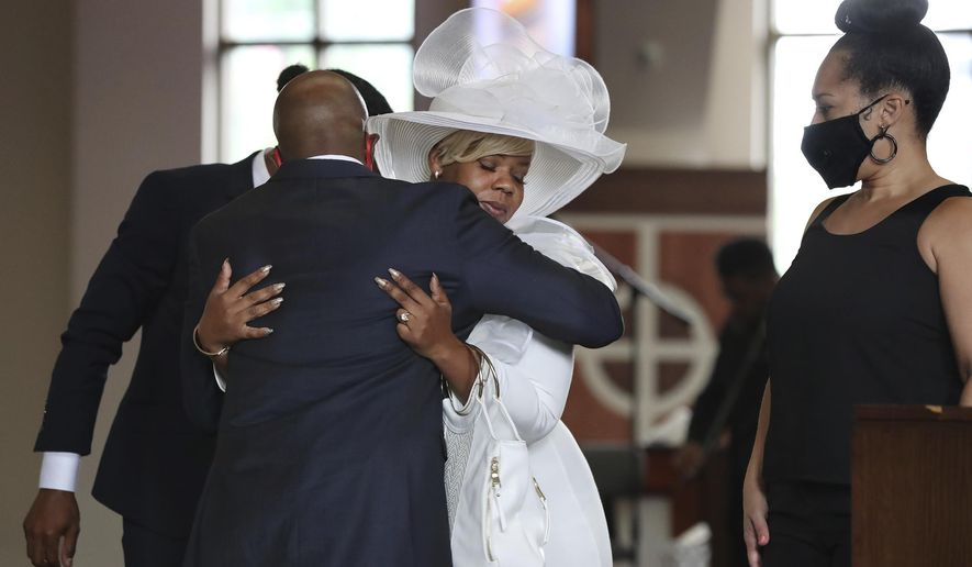 The Rev. Raphael G. Warnock, senior pastor of Ebenezer Baptist Church, comforts Tomika Miller, the wife of Rayshard Brooks during his public viewing at Ebenezer Baptist Church on Monday, Jun 22, 2020, in Atlanta. Brooks, 27, died June 12 after being shot by an officer in a Wendy's parking lot. Brooks' death sparked protests in Atlanta and around the country. A private funeral for Brooks will be held Tuesday at the church. (Curtis Compton/Atlanta Journal-Constitution via AP, Pool)