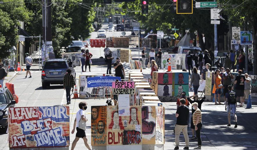 Pedestrians wander through barricaded streets Tuesday, June 23, 2020, in Seattle, where streets are blocked off in what has been named the Capitol Hill Occupied Protest zone. Faced with growing pressure to crack down on the area following two weekend shootings, Seattle's mayor said Monday that officials will move to wind down the blocks-long span of city streets taken over two weeks ago. (AP Photo/Elaine Thompson)