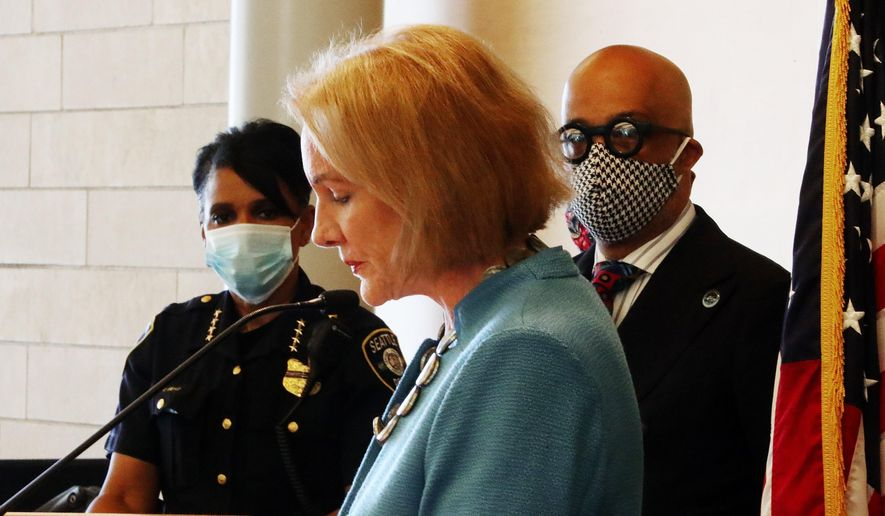 """Seattle Mayor Jenny Durkan, center, pauses while speaking, as Chief of Police Carmen Best, left, listens during a news conference Monday, June 22, 2020, in Seattle. Durkan said the city is working with the community to bring the """"Capitol Hill Occupied Protest"""" zone to an end. (Ken Lambert/The Seattle Times via AP)"""