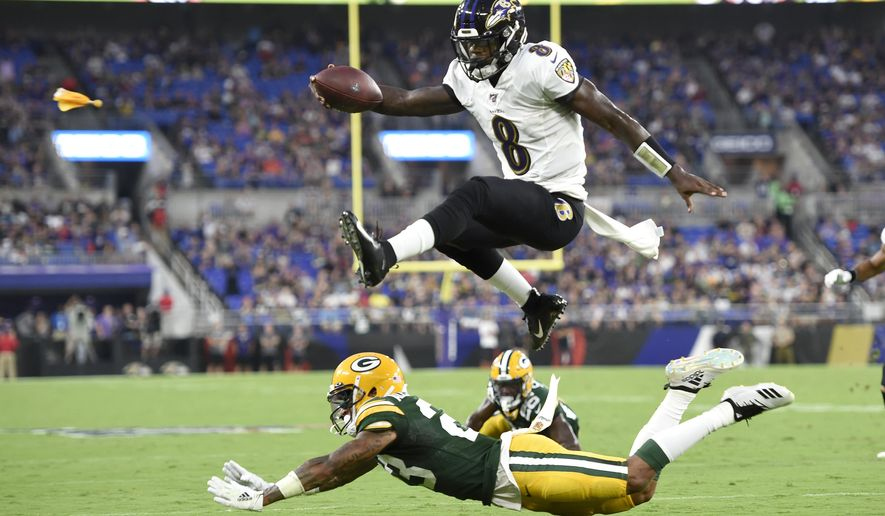 In this Aug. 15, 2019, file photo, Baltimore Ravens quarterback Lamar Jackson (8) leaps over Green Bay Packers cornerback Jaire Alexander (23) during the first half of a NFL football preseason game, in Baltimore. Ravens offensive coordinator Greg Roman is tweaking and refining a record-setting unit led by NFL MVP Lamar Jackson, who is expected to again be the key component of an attack with several newcomers in the mix.  (AP Photo/Gail Burton, File)  **FILE**