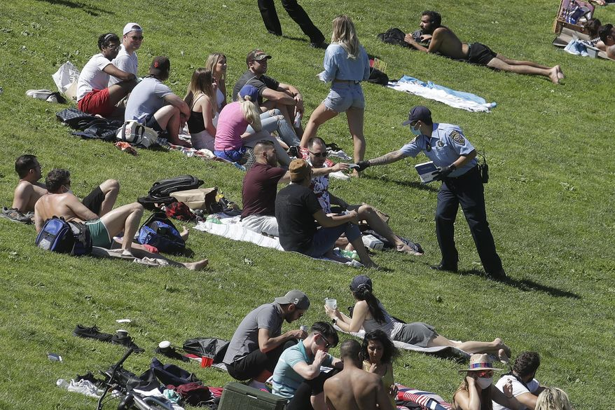 """In this May 24, 2020, file photo, a San Francisco Police cadet hands out face masks to help prevent the spread of the coronavirus, at Dolores Park in San Francisco. Health officials in Santa Clara County, California, one of the most aggressive in the nation in shutting down because of the coronavirus are warning of """"worrisome"""" growing infections tied in the San Francisco Bay Area as California reports its highest one-day total infections amid a rise in hospitalizations from the virus. (AP Photo/Jeff Chiu, File)"""