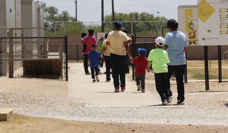 In this Aug. 23, 2019, file photo, immigrants seeking asylum hold hands as they leave a cafeteria at the ICE South Texas Family Residential Center in Dilley, Texas. (AP Photo/Eric Gay, File) ** FILE **