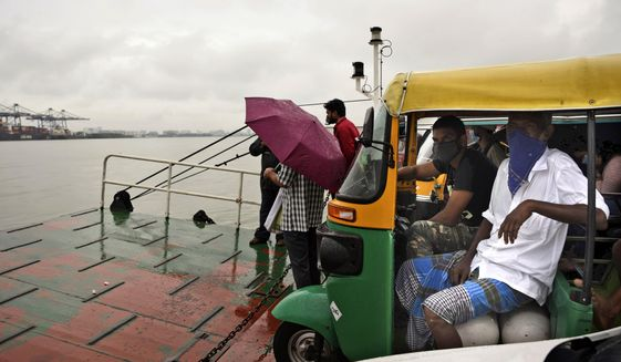 Commuters wearing masks as a precaution against the coronavirus travel in a ferry during rain in Kochi, Kerala state, India, Monday, June 22 2020. India is the fourth hardest-hit country by the COVID-19 pandemic in the world after the U.S., Russia and Brazil. (AP Photo/R S Iyer)