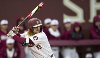 Florida State NCAA college baseball outfielder Elijah Cabell (19) bats against the Univ. of Cincinnati, Friday, Feb. 21, 2020, in Tallahassee, Fla. If all had gone as he hoped, Cabell and his Florida State teammates would be playing for the College World Series championship this week. Instead, Cabell treks to a ball field in his neighborhood in Winter Park, Florida, most days to work on his game in solitude.  (Alicia Devine/Tallahassee Democrat via AP)  **FILE**