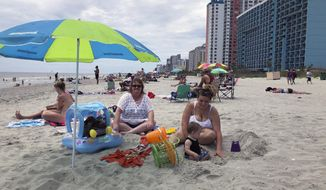 """Christy Kasler, center, from Ohio, enjoys a day at the beach, Thursday, June 18, 2020, while her daughter-in-law Cory plays with her grandson, Bentley, in Myrtle Beach, S.C. Across America, people are leaving their cares — and sometimes their masks — at home after months of worry about the virus as Southern states like South Carolina open hotels and restaurants and like Myrtle Beach advertise """"Yes, the beach is open!""""  (AP Photo/Jeffrey Collins)"""