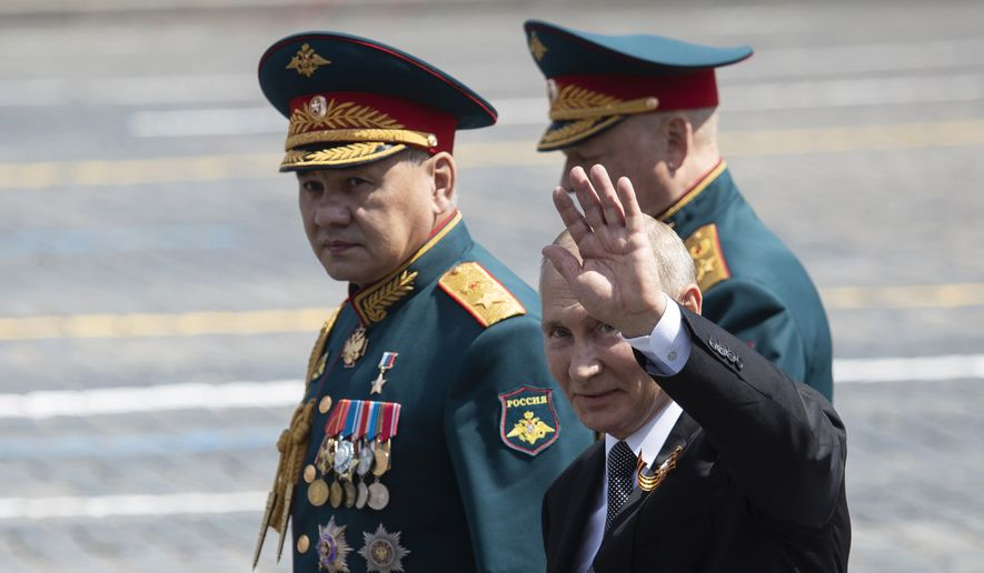 Russian President Vladimir Putin, center, and, Defense Minister Sergei Shoigu, left, leave Red Square after the Victory Day military parade marking the 75th anniversary of the Nazi defeat in Moscow, Russia, Wednesday, June 24, 2020. Russian President Vladimir Putin hailed the defeat of Nazi Germany at the traditional massive Red Square military parade, which was delayed by more than a month because of the invisible enemy of the coronavirus. The parade is usually held May 9 on Victory Day, Russia's most important secular holiday but was postponed until Wednesday due to the pandemic. (AP Photo/Pavel Golovkin, Pool)