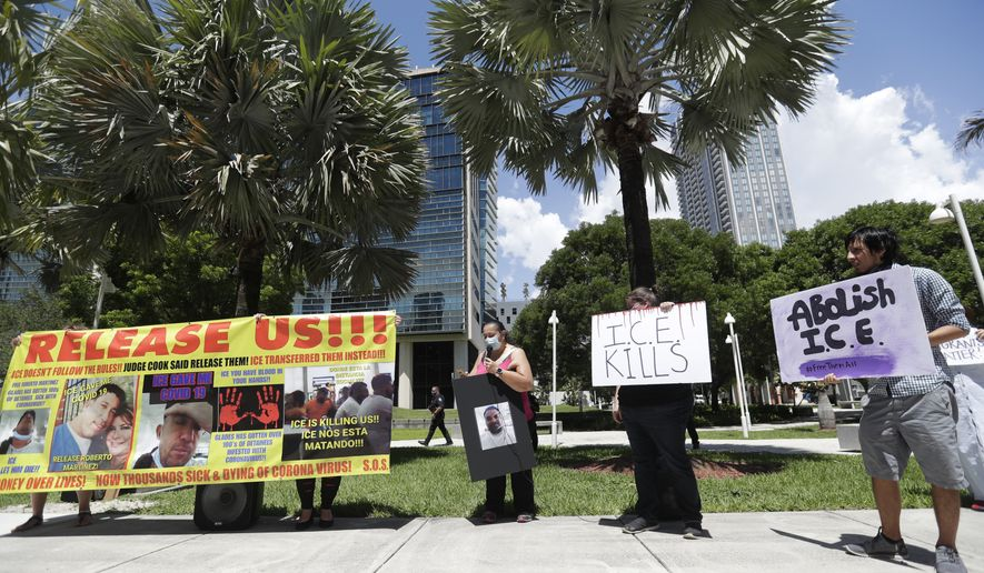 Demonstrators chant and hold signs, Wednesday, June 24, 2020, outside the Wilkie D. Ferguson Jr. U.S. Courthouse in Miami. Immigrant rights groups are protesting conditions at ICE detention centers due to the potential spread of the coronavirus. (AP Photo/Wilfredo Lee)