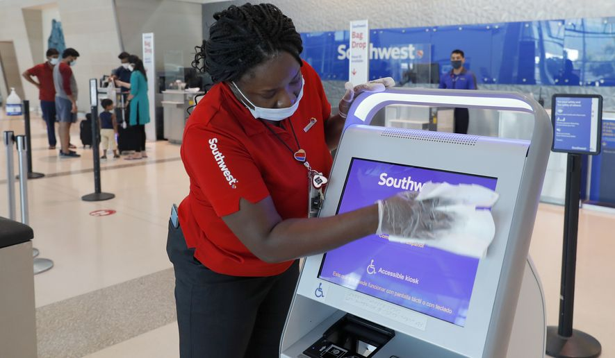 Southwest Airlines employee La Toya Malone Key wipes down a kiosk after it was used by a passenger to secure their boarding pass at Love Field in Dallas, Wednesday, June 24, 2020. (AP Photo/Tony Gutierrez)