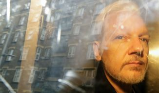 In this May 1, 2019, file photo, buildings are reflected in the window as WikiLeaks founder Julian Assange is taken from court in London. (AP Photo/Matt Dunham, File)