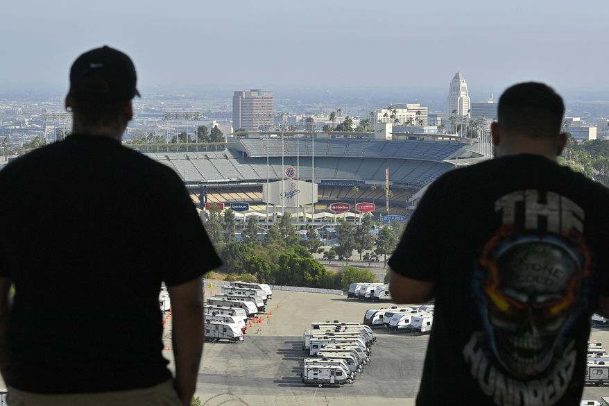 Los Angeles Dodgers fans take in the view near Dodger Stadium on Wednesday, June 24, 2020, in Los Angeles. By the time Major League Baseball returns in late July, it will have been more than four months since teams last played. The season is now going to be a 60-game sprint to the finish, held in ballparks without fans and featuring some unusual rules. (AP Photo/Mark J. Terrill)  **FILE***