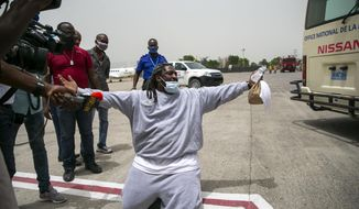 Sony Remond, a Haitian who has just been deported from the United States kneels on the tarmac at the Toussaint Louverture International Airport, before he is to be transported to a hotel to undergo a 14-day mandated quarantine, in Port-au-Prince, Haiti, Tuesday, June 23, 2020. ( AP Photo/Dieu Nalio Chery)