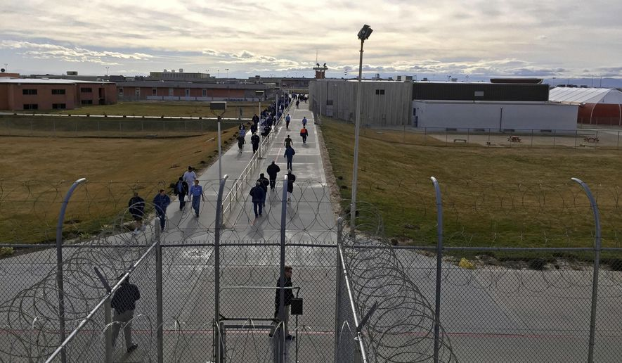 In this Jan. 30, 2018, file photo, inmates walk across the grounds of the Idaho State Correctional Institution in Kuna, Idaho. Hundreds of thousands of dollars in coronavirus relief payments have been sent to people behind bars across the United States, and now the IRS is asking state officials to help claw back the cash that the federal tax agency says was mistakenly sent. (AP Photo/Rebecca Boone, File)