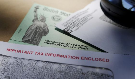 In this April 23, 2020, file photo, President Donald Trump's name is seen on a stimulus check issued by the IRS to help combat the adverse economic effects of the COVID-19 outbreak, in San Antonio. (AP Photo/Eric Gay) ** FILE **