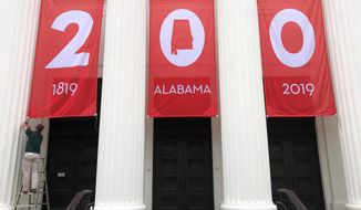"""In this Feb. 28, 2019, photo a worker adjusts a banner celebrating Alabama's bicentennial outside the Department of Archives and History in Montgomery, Ala. Alabama's main state history agency is acknowledging that it helped perpetuate systemic racism by promoting Confederate narratives while ignoring those of Black people, a """"statement of recommitment"""" issued Tuesday, June 23, 2020 by the Alabama Department of Archives and History said. (AP Photo/Jay Reeves, File)"""