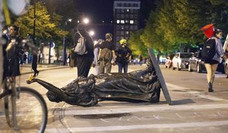 "Wisconsin's ""Forward"" statue lies in the street on Capitol Square in Madison, Wis. Tuesday, June 23, 2020.  Crowds outside the Wisconsin State Capitol tore down two statues and attacked a state senator amid protests following the arrest of a Black man who shouted at restaurant customers through a megaphone while carrying a baseball bat.  (Emily Hamer/Wisconsin State Journal via AP)"