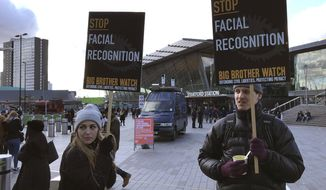 FILE - In this Feb. 11, 2020, file photo, Silkie Carlo, left, demonstrates in front of a mobile police facial recognition facility outside a shopping centre in London. A Black man who says he was unjustly arrested because facial recognition technology mistakenly identified him as a suspected shoplifter is calling for a public apology from Detroit police. And for the department to abandon its use of the controversial technology. (AP Photo/Kelvin Chan, File)