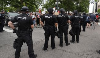 In this May 29, 2020, photo, Denver Police officers form a line of defense as they square off with participants in a protest over the death of George Floyd. (AP Photo/David Zalubowski) **FILE**