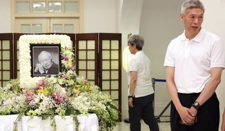 FILE - In this March 24, 2015, file photo, Prime Minister Lee Hsien Loong's brother, Lee Hsien Yang, right, receives friends and family members paying their respects to the late Lee Kuan Yew during a private family wake at the Istana or Presidential Palace in Singapore. Lee Hsien Yang, joined the opposition Progress Singapore Party on Wednesday, June 24, 2020, ahead of July 10 general elections but declined to say if he was going to run. (AP Photo/Wong Maye-E, File)