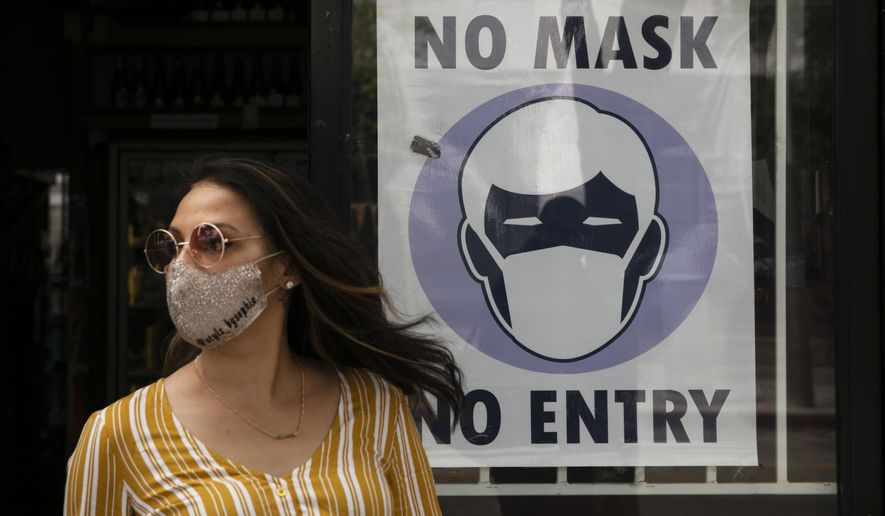 A woman walks out of a liquor store past a sign requesting its customers to wear a mask Tuesday, June 23, 2020, in Santa Monica, Calif. The state Department of Public Health recorded more than 5,000 new cases Tuesday, putting the total number of positive cases at more than 183,000. The state has seen more than 5,500 deaths related to COVID-19. (AP Photo/Jae C. Hong)