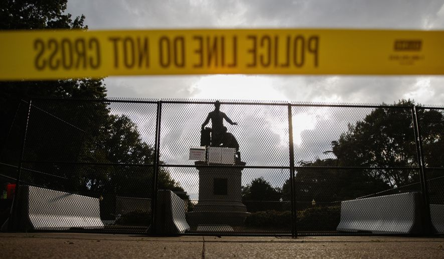 Yellow police tape, concrete barricades and fencing surround the Emancipation Memorial in Lincoln Park in Washington, Thursday, June 25, 2020. The Emancipation Memorial depicts a freed slave kneeling at the feet of President Abraham Lincoln. Calls are intensifying for the removal of the statue as the nation confronts racial injustice. (AP Photo/Carolyn Kaster)
