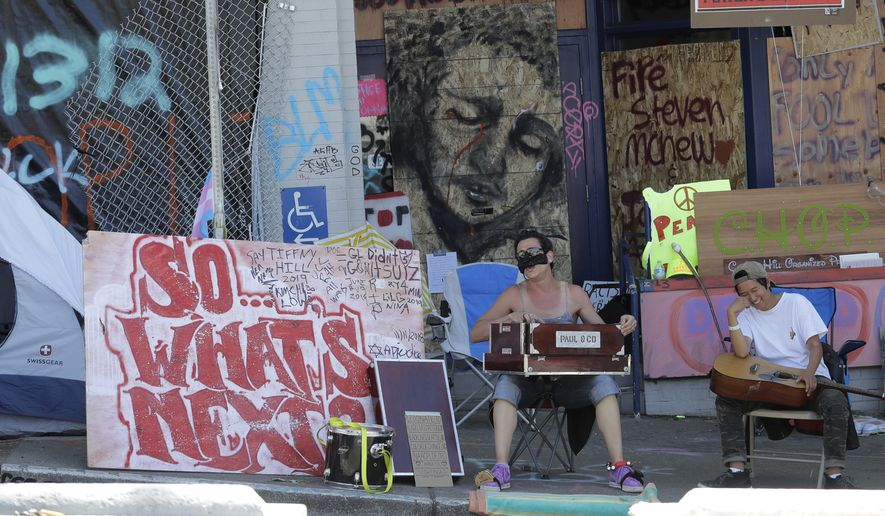 """Two people perform music next to a sign in front of the Seattle Police Department's East Precinct building in the CHOP (Capitol Hill Occupied Protest) zone reads """"So What's Next?"""" Thursday, June 25, 2020, in Seattle. The area has been occupied by Black Lives Matter protesters since police pulled back from the building following violent clashes with demonstrators, and the future of the protest area has been in question since Seattle Mayor Jenny Durkan said earlier in the week that police intend to eventually return to the building. (AP Photo/Ted S. Warren)"""