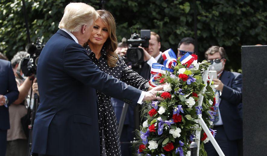 President Donald Trump, accompanied by first lady Melania Trump, places a wreath at the Korean War Veterans Memorial, Thursday, June 25, 2020, in Washington. (AP Photo/Alex Brandon)