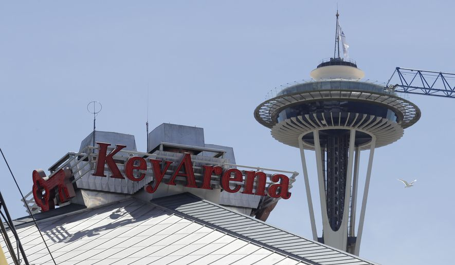 The top of the roof of KeyArena, which is currently undergoing a complete renovation, is shown with the Space Needle in the background, Thursday, June 25, 2020, in Seattle. Amazon has bought the naming rights to the arena, which will host a new NHL hockey team and the WNBA Basketball Seattle Storm, and will call the facility Climate Pledge Arena. (AP Photo/Ted S. Warren)