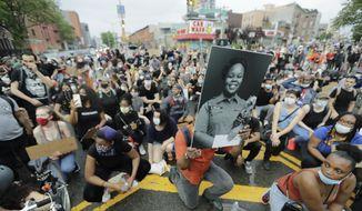 A man holds a photograph of Breonna Taylor on her birthday as he kneels with other protesters on Atlantic Avenue during a solidarity rally for George Floyd on Atlantic Avenue, Friday, June 5, 2020, in the Brooklyn borough of New York. Taylor, a black woman, was fatally shot by police in her home in March and Floyd, a black man, died after being restrained by Minneapolis police officers on May 25. (AP Photo/Frank Franklin II)