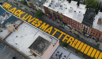 """In this June 15, 2020, file photo, a sign reading """"Black Lives Matter,"""" is painted in orange on Fulton Street in the Brooklyn borough of New York. On Thursday, June 25, 2020, President Donald Trump used Twitter to voice his displeasure with New York City Mayor Bill de Blasio's plan to paint """"Black Lives Matter"""" in front of Trump's namesake Manhattan tower. (AP Photo/John Minchillo, File)"""