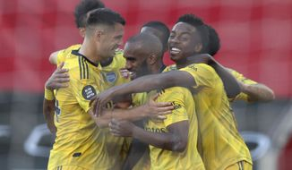 Arsenal's Joe Willock, right, celebrates with his teammates after scoring his side's second goal during the English Premier League soccer match between Southampton and Arsenal at St Mary's Stadium, in Southampton, England, Thursday, June 25, 2020. (Andrew Matthews/Pool via AP)