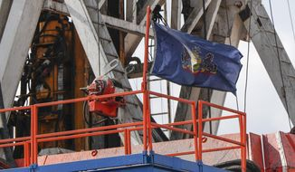 In this file photo from March 12, 2020, the flag of the Commonwealth of Pennsylvania flies on the drilling rig as work continues at a shale gas well drilling site in St. Mary's, Pa. (AP Photo/Keith Srakocic, File)  **FILE**