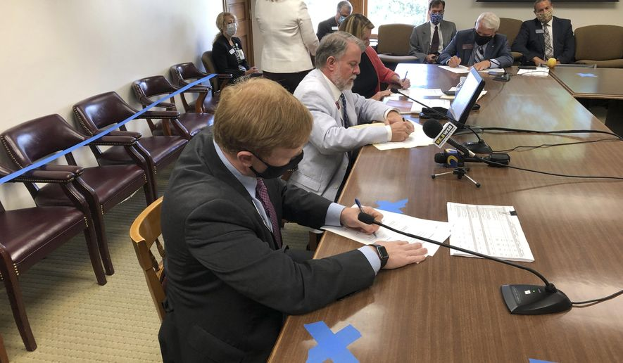 Senate Appropriations Committee Chairman Blake Tillery, left, and House Appropriations Committee Chairman Terry England sign a final agreement on Georgia's state budget on Thursday, June 25, 2020. England and Tillery say they tried to avoid budget cuts that would most directly harm citizens even as they reduced state spending by more than $2 billion. (AP Photo/Jeff Amy)