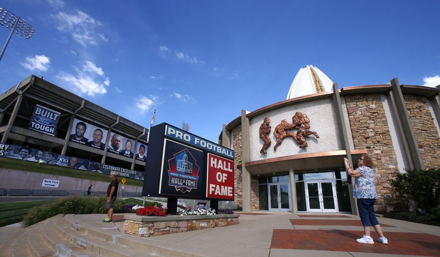 In this Aug. 7, 2015, file photo, a visitor to the Pro Football Hall of Fame pauses to take a photo of the sign in front in Canton, Ohio. The NFL has canceled the Hall of Fame game that traditionally opens the preseason and is delaying the 2020 induction ceremonies because of the coronavirus pandemic, two people with direct knowledge of the decision told The Associated Press on Thursday, June 25, 2020. The people spoke to the AP on condition of anonymity because the decision has not been publicly announced, though an announcement is expected later Thursday. (AP Photo/Gene J. Puskar, File)  **FILE**