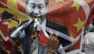 A Karni Sena supporter tears a banner featuring Chinese President Xi Jinping and shout slogans during a protest against China in Ahmedabad, India, Wednesday, June 24, 2020. Chinese and Indian military commanders have agreed to disengage their forces in a disputed area of the Himalayas following a clash that left at least 20 soldiers dead, both countries said Tuesday. The commanders reached the agreement Monday in their first meeting since the June 15 confrontation, the countries said. (AP Photo/Ajit Solanki)