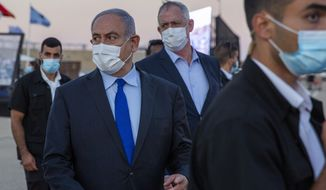 Israeli Prime Minister Benjamin Netanyahu, front, and Israeli Defense Minister Benny Gantz wearing face masks attend a graduation ceremony for new pilots in Hatzerim air force base near the southern Israeli city of Beersheba, Israel, Thursday, June 25, 2020. (AP Photo/Ariel Schalit, Pool)
