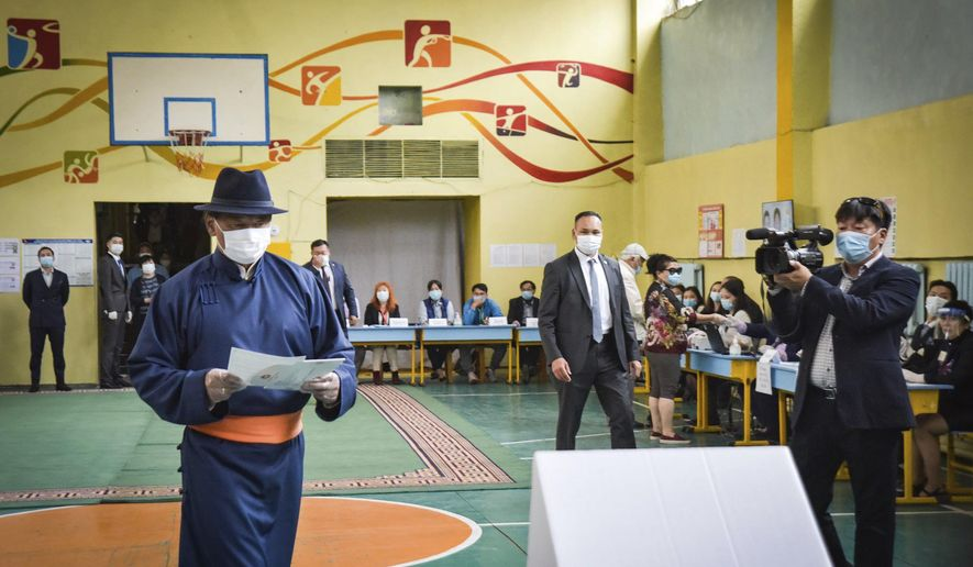 In this photo released by Xinhua News Agency, Mongolian Prime Minister Ukhnaa Khurelsukh at left prepare to cast his vote at a polling station in Ulaanbaatar, Mongolia, on Wednesday, June 24, 2020. Mongolians were voting in parliamentary elections Wednesday across the vast, lightly populated country, a U.S. ally squeezed between authoritarian governments in China and Russia. The polls are being held amid considerable success in the country's fight against the coronavirus, with just 215 cases of COVID-19 recorded. All of them have been imported and no one has died. (Chadraabal/Xinhua via AP)