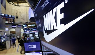 In this March 22, 2017, photo, the Nike logo appears above the post where it trades on the floor of the New York Stock Exchange. (AP Photo/Richard Drew) **FILE**