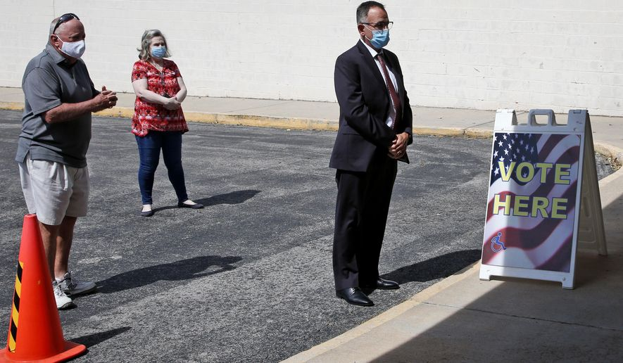 Oklahoma State Treasurer Randy McDaniel, right, practices social distancing with other voters as he waits to vote in early voting for Oklahoma's June 30th primary and special election, at the Oklahoma County Election Board, in Oklahoma City, Thursday, June 25, 2020. (AP Photo/Sue Ogrocki)